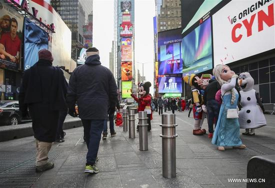 Pedestrians walk past metal bollards at Times Square in New York, the United States, on Jan. 3, 2018. New York City plans to install 1,500 new security barriers in high-profile locations to guard against vehicle attacks and other terror-related incidents. (Xinhua/Wang Ying)