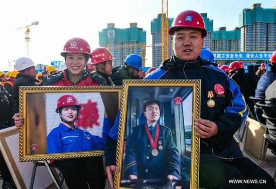 Bus driver Zhang Songping (R) and subway construction worker Cui Ya'nan display their portrait photos in Beijing, capital of China, Jan. 9, 2018. A team consisted of press photographers and photographic enthusiasts volunteered to make portraits for workers on their jobs from construction and other industries. More than 1,000 workers received their photos on Tuesday. (Xinhua/Li Xin)