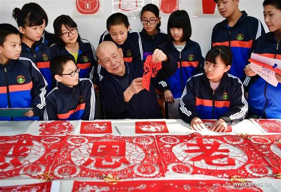 Wang You (C front), a paper cutting artisan, teaches students at Hengqu experimental middle school in Luanxian County, north China's Hebei Province, Dec. 29, 2017. The local government has encouraged schools to open paper cutting class to teach the youth traditional cultures. (Xinhua/Mu Yu)