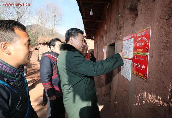 Chinese President Xi Jinping, also general secretary of the Communist Party of China Central Committee and chairman of the Central Military Commission, watches a poverty-alleviation contact card as he visits Sanhe Village of Sanchahe Township in Zhaojue County of Liangshan Yi Autonomous Prefecture, southwest China's Sichuan Province, Feb. 11, 2018. Xi made an inspection tour in Sichuan and extended greetings ahead of the Spring Festival, which falls on Feb. 16 this year. (Xinhua/Xie Huanchi)
