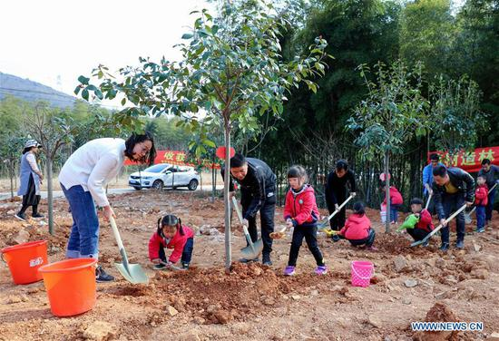 Children shovel soil under the guidance of their teachers and parents during a tree planting activity at Lijiaxiang Township of Changxing County, east China's Zhejiang Province, March 12, 2018. A tree planting activity aimed at fostering children's awareness about environmental protection was held here. (Xinhua/Xu Xu)