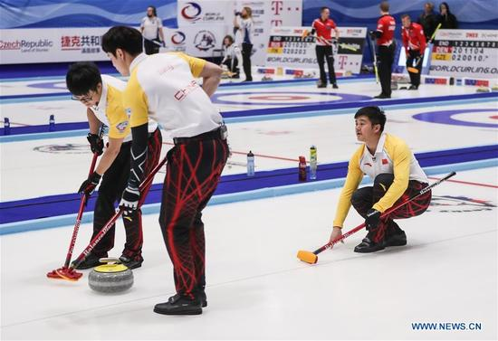 China's Xu Xiaoming (R) casts stone during an Olympic Qualification match of curling for 2018 Winter Olympics in Pyeongchang between men's teams from China and Italy, in Pilsen, the Czech Republic, on Dec. 6, 2017. China won 10-5. (Xinhua/Shan Yuqi)