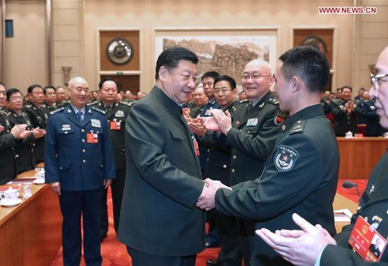 Chinese President Xi Jinping, also general secretary of the Communist Party of China (CPC) Central Committee and chairman of the Central Military Commission, shakes hands with deputies from People's Liberation Army (PLA) and armed police before attending a plenary meeting of the delegation of PLA and armed police at the ongoing session of the 13th National People's Congress in Beijing, capital of China, March 12, 2018. (Xinhua/Li Gang)