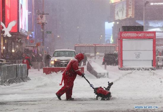 A worker clears snow at Times Square in New York, the United States, Jan. 4, 2018. New York State Governor Andrew Cuomo has declared state of emergency for the entire downstate region on Thursday as a snow storm continued to pound the U.S. East Coast. (Xinhua/Wang Ying)