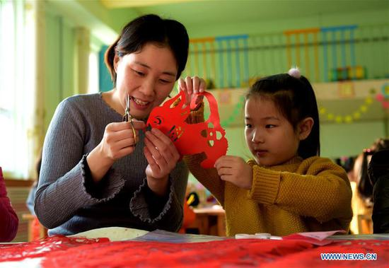 A girl learns paper-cutting to greet the upcoming Chinese lunar New Year at a kindergarten in Hengshui City, north China's Hebei Province, Feb. 4, 2018. The Chinese lunar year for 2018 is the Year of the Dog and this year's Spring Festival falls on Feb. 16. (Xinhua/Wang Xiao)