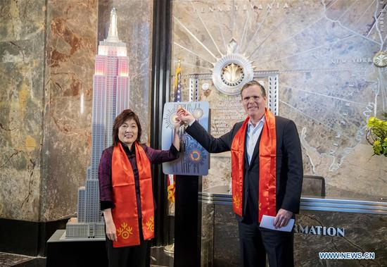 Chinese Consul General in New York Zhang Qiyue (L) and John B. Kessler, President of the Empire State Realty Trust, flip the switch to light the model of Empire State Building at a ceremonial lighting ceremony in honor of the Spring Festival at the Empire State Building in New York, the United States, on Feb. 13, 2018. The top of the Empire State Building in Midtown Manhattan, New York, will shine in red and gold at sunset on Tuesday and Thursday, celebrating the Chinese Lunar New Year that falls on Feb. 16 this year. (Xinhua/Wang Ying)