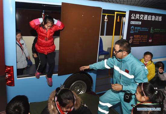 Children attend a training session on public transport evacuation at a home safety training center in Qingdao, east China's Shandong Province, March 7, 2018. The Qingdao Municipal Women's Federation organized a home safety workshop on Wednesday, allowing participants to learn home safety knowledge and skills via on-the-spot training sessions. (Xinhua/Li Ziheng)