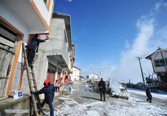 Staff members of Wuchuan Power Supply Bureau help local villagers with supply lines in Wuchuan Gelao and Miao Autonomous County, southwest China's Guizhou Province, Jan. 9, 2018. According to China Southern Power Grid Guizhou Bureau, 256 on-line alert terminal devices are launched to make sure the stable operation of power supply, since they issued a blue alert for ice weather on Jan. 6. (Xinhua/Tao Liang)
