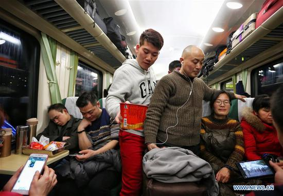 A passenger holding a bowl of instant noodles shoulder his way to his seat as he takes the train Z1 from China's capital Beijing to central China's Changsha in Hunan Province, Feb. 12, 2018. The number of passenger trips around China hit 108.363 million from Feb. 1 to Feb. 12 this year. The Spring Festival travel rush began on Feb. 1 and will last until March 12. The China National Tourism Administration said that 385 million trips, mostly domestic, are expected to be made during the Spring Festival 2018, up 12 percent year on year. (Xinhua/Zeng Tao)