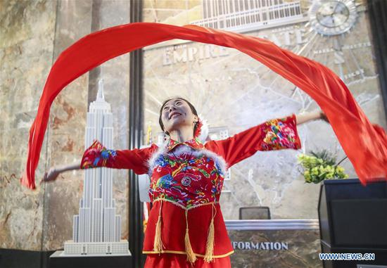 A dancer performs prior to a ceremonial lighting ceremony in honor of the Spring Festival at the Empire State Building in New York, the United States, on Feb. 13, 2018. The top of the Empire State Building in Midtown Manhattan, New York, will shine in red and gold at sunset on Tuesday and Thursday, celebrating Chinese Lunar New Year that falls on Feb. 16 this year. (Xinhua/Wang Ying)