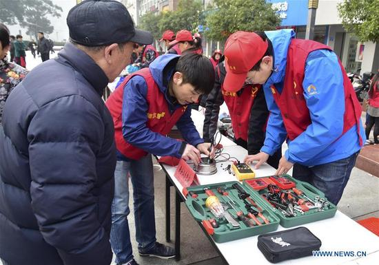 Volunteers repair electric appliances in Jiande City, east China's Zhejiang Province, Dec. 5, 2017, the international volunteer day. (Xinhua/Ning Wenwu)
