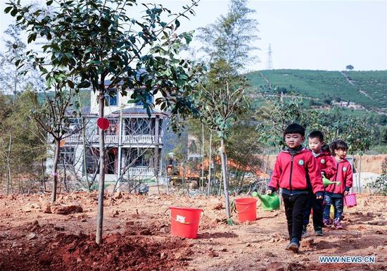 Children bring water during a tree planting activity at Lijiaxiang Township of Changxing County, east China's Zhejiang Province, March 12, 2018. A tree planting activity aimed at fostering children's awareness about environmental protection was held here. (Xinhua/Xu Xu)