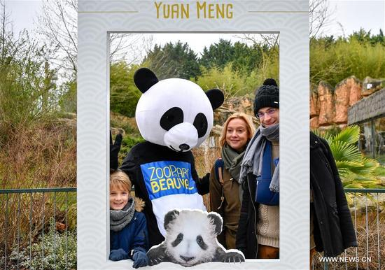 """Visitors pose for photo with a panda figure at the Zooparc de Beauval in Saint-Aignan, France on Jan. 13, 2018. The first panda cub born in France """"Yuan Meng"""" debuts with the public on Saturday morning. (Xinhua/Chen Yichen)"""
