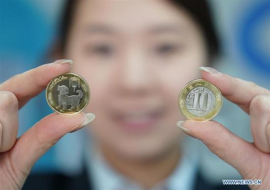 A bank clerk displays commemorative coins for the Year of the Dog in Beijing, capital of China, Feb.2, 2018. The People's Bank of China issued commemorative 10-yuan coins on Friday. (Xinhua/Zhang Yuwei)