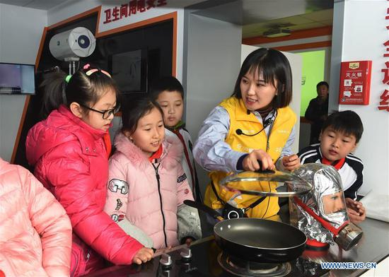 An instructor explains kitchen fire emergency measures to children at a home safety training center in Qingdao, east China's Shandong Province, March 7, 2018. The Qingdao Municipal Women's Federation organized a home safety workshop on Wednesday, allowing participants to learn home safety knowledge and skills via on-the-spot training sessions. (Xinhua/Li Ziheng)