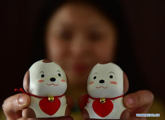 A craftswoman displays Huishan clay figurines featuring the Chinese lunar New Year of Dog in Wuxi City, east China's Jiangsu Province, Feb. 2, 2018. (Xinhua/Huan Yueliang)