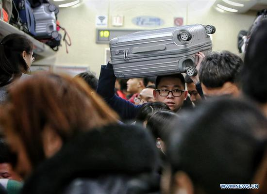 A passenger carries a suitcase over his head as he shoulders his way to take the train Z1 from China's capital Beijing to central China's Changsha in Hunan Province, Feb. 12, 2018. The number of passenger trips around China hit 108.363 million from Feb. 1 to Feb. 12 this year. The Spring Festival travel rush began on Feb. 1 and will last until March 12. The China National Tourism Administration said that 385 million trips, mostly domestic, are expected to be made during the Spring Festival 2018, up 12 percent year on year. (Xinhua/Zeng Tao)