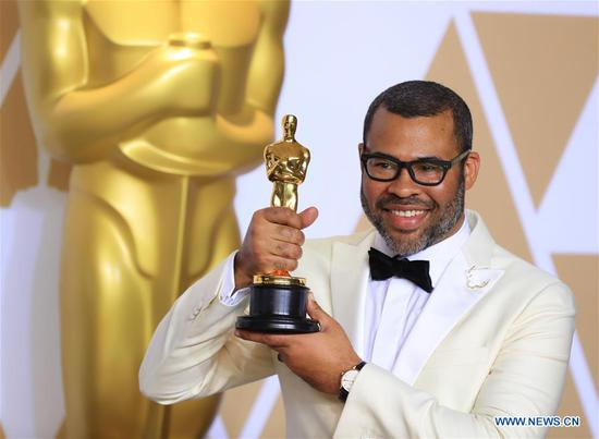 Director Jordan Peele poses after winning the Best Original Screenplay award for