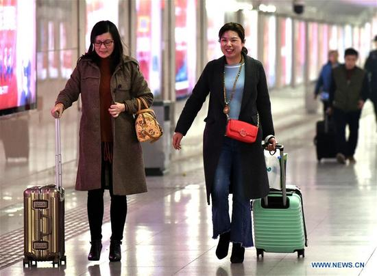 Two passengers leave Zhengzhou Railway Station in Zhengzhou, central China's Henan Province, March 12, 2018. China's 2018 Spring Festival travel season came to an end on Monday. The period, also known as
