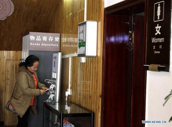 A visitor charges her cellphone in a public toilet in Xijiang Qianhu Miao Village in Leishan County, southwest China's Guizhou Province, Dec. 5, 2017. The Chinese government launched its