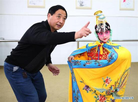 A pupil of Xichang Elementary School practices Peking Opera with the guidance of a teacher in Chengdong Town of Hai'an County in Nantong City, east China's Jiangsu Province, Jan. 2, 2018. The school set up a Peking Opera club and invites professional performers to teach the children. (Xinhua/Xiang Zhonglin)