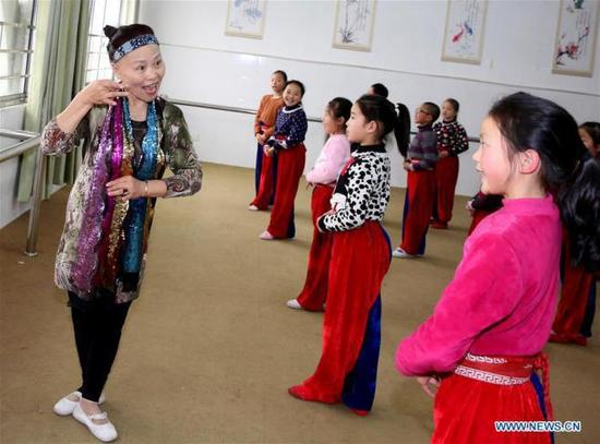 A teacher teaches pupils of Xichang Elementary School to perform Peking Opera in Chengdong Town of Hai'an County in Nantong City, east China's Jiangsu Province, Jan. 2, 2018. The school set up a Peking Opera club and invites professional performers to teach the children. (Xinhua/Xiang Zhonglin)