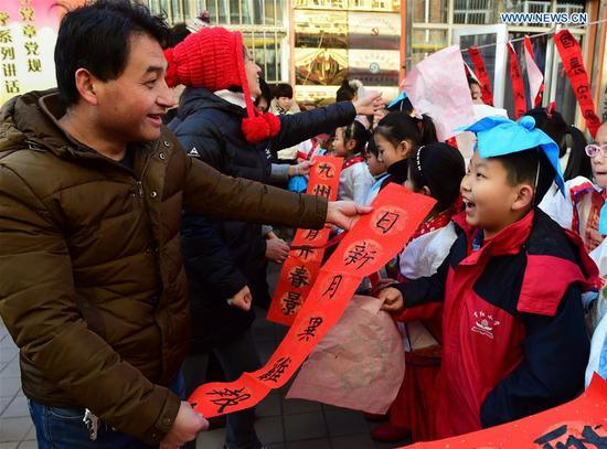 Pupils of Chinese calligraphy hobby group give Spring Festival couplets to residents in a community in Cangzhou, north China's Hebei Province, Feb. 5, 2018. (Xinhua/Fu Xinchun)