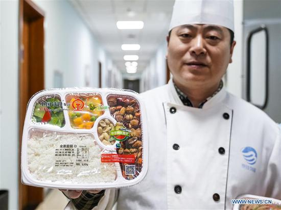 A chef shows a new kind of vegetarian set meal of high-speed trains at a food production base in Beijing, capital of China, Feb. 7, 2018. Altogether 18 kinds of set meals at 6 price levels are available on China's high-speed trains during the Spring Festival travel rush which is from Feb. 1 to March 12. (Xinhua/Shen Bohan)