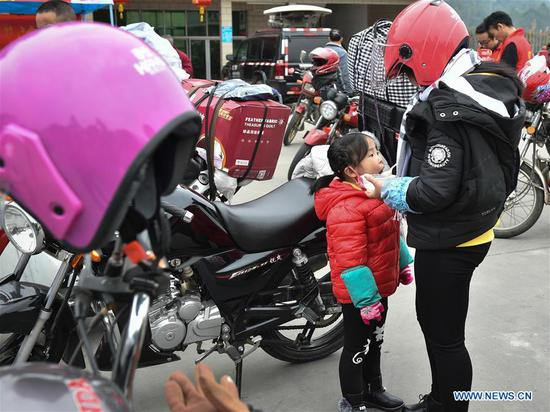 A mother feeds her child at Xiaoxiang service station in Zhaoqing, south China's Guangdong Province, Feb. 7, 2018. Many migrant workers in China chose to go home by motorcycle for a family reunion in the Spring Festival, or Chinese traditional lunar New Year. (Xinhua/Liang Xu)