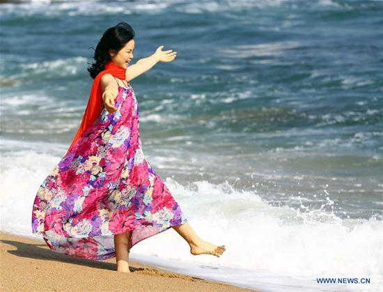 A tourist has fun by the seaside in Sanya, south China's Hainan Province, Feb. 13, 2018. (Xinhua/Chen Wenwu)
