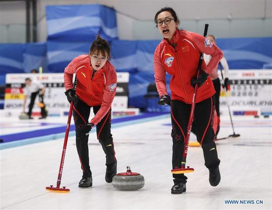 China's Zhou Yan (R) and Ma Jingyi compete during an Olympic Qualification match of curling for 2018 Winter Olympics in Pyeongchang between women's teams from China and Latvia in Pilsen, the Czech Republic, on Dec. 6, 2017. China won 11-5. (Xinhua/Shan Yuqi)