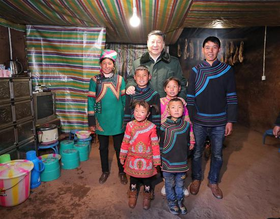 Chinese President Xi Jinping, also general secretary of the Communist Party of China Central Committee, poses for a group photo with an impoverished family as he visits Sanhe Village of Sanchahe Township in Zhaojue County of Liangshan Yi Autonomous Prefecture, southwest China's Sichuan Province, Feb. 11, 2018. Xi made an inspection tour in Sichuan Province on Feb. 11. (Xinhua/Xie Huanchi)