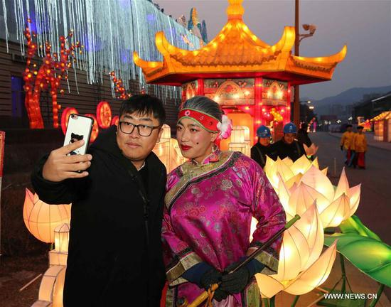 A tourist takes selfie with a performer at a lantern fair to greet the upcoming Lantern Festival in Chengde City, north China's Hebei Province, Feb. 27, 2018. The Lantern Festival falls on the 15th day of the first lunar month, or March 2 this year. (Xinhua/Chen Yuewei)