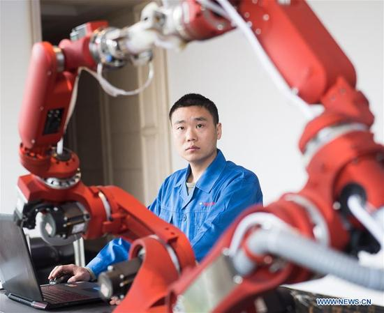 A technician from Rui'an Hsoar Group debugs a robot in Rui'an City, east China's Zhejiang Province, Jan. 16, 2018. Over 30 enterprises in Rui'an City purchased more than 500 robots to boost productivity. (Xinhua/Weng Xinyang)