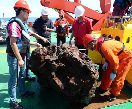 Expedition team members observe a sulfide sample collected from the south Atlantic on Nov. 30, 2017. Xiangyanghong 01, China's elite science ship, on Thursday collected the sulfide sample weighed around 3 tons, which is the biggest one of its kind in the country. (Xinhua/Zhang Xudong)
