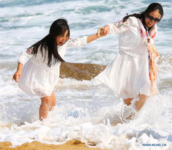Tourists have fun by the seaside in Sanya, south China's Hainan Province, Feb. 13, 2018. (Xinhua/Chen Wenwu)