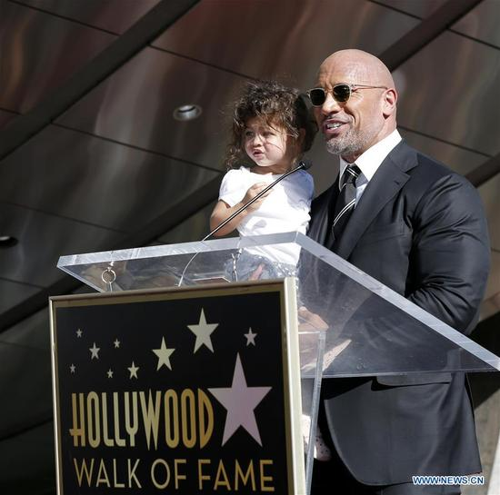 Dwayne Johnson holds his daughter as he speaks at his Hollywood Walk of Fame Star ceremony in Los Angeles, the United States, Dec. 13, 2017. Dwayne Johnson was honored with a star on the Hollywood Walk of Fame on Monday. (Xinhua/Li Ying)