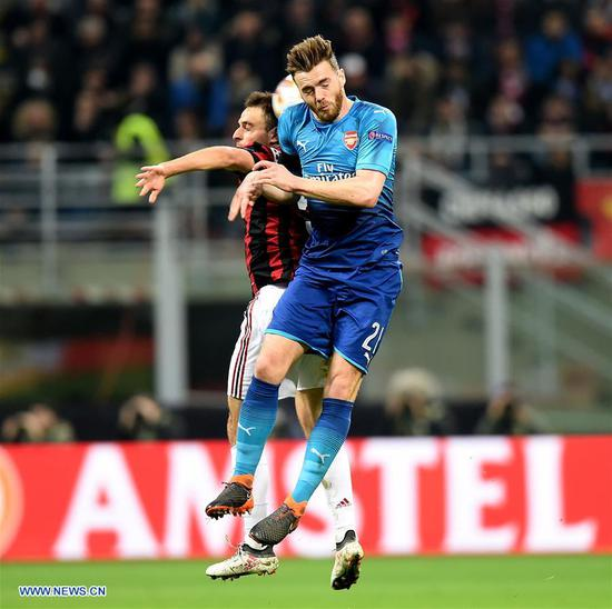 AC Milan's Hakan Calhanoglu (L) competes with Arsenal's Jack Wilshere during a Europa League round of 16 first leg soccer match between AC Milan and Arsenal at the San Siro stadium in Milan, Italy, March 8, 2018. Arsenal won 2-0. (Xinhua/Alberto Lingria)
