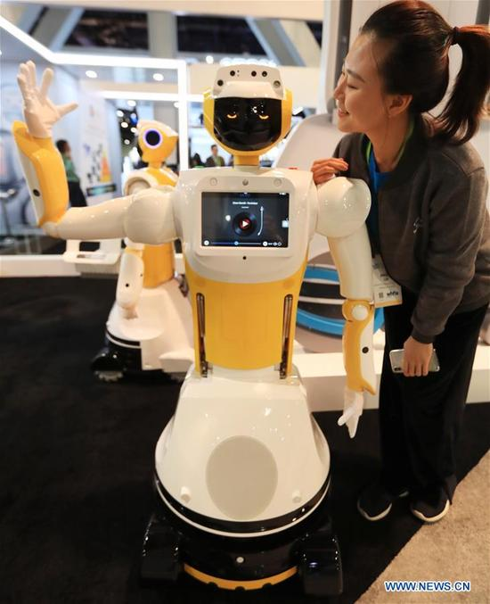 A staff member poses for photos with a Robot named Sanbo Max and produced by Chinese company Qihan at Consumer Electronics Show (CES) in Las Vegas, the United States, Jan. 10, 2018. (Xinhua/Li Ying)
