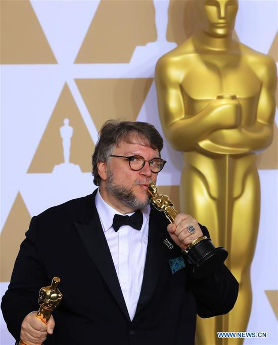 Director Guillermo del Toro poses after winning the Best Director award and the Best Picture award for
