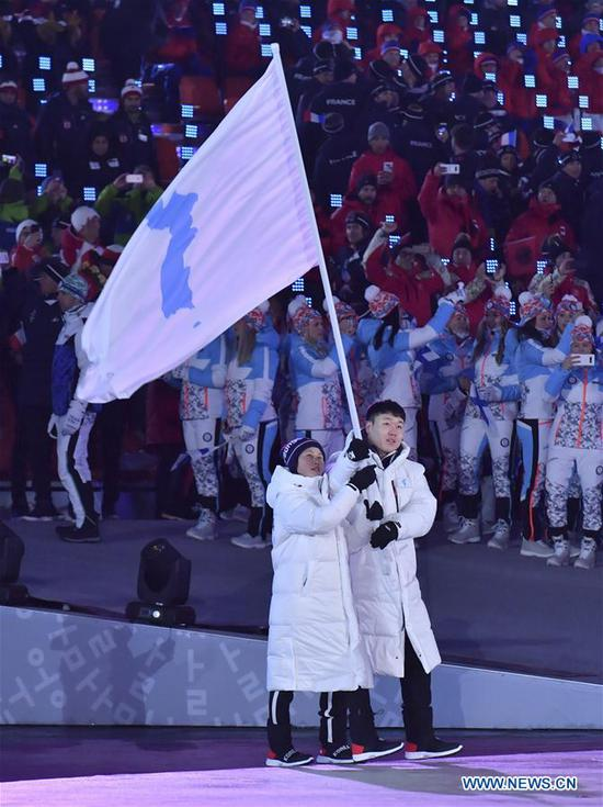 Flag bearer of the Democratic People's Republic of Korea (DPRK) Hwang Chung-gum (L) and flag bearer of South Korea Won Yun-jong march together under a unified Korean flag during the opening ceremony of the 2018 PyeongChang Winter Olympic Games at PyeongChang Olympic Stadium in PyeongChang, South Korea, Feb. 9, 2018. (Xinhua/Lui Siu Wai)