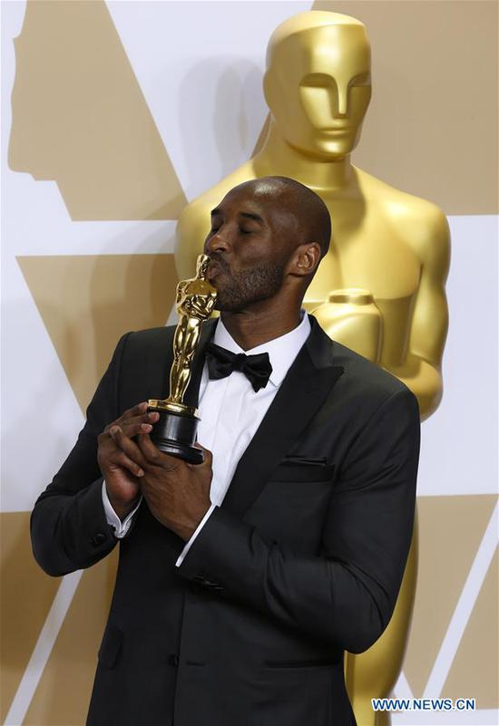 Former U.S. basketball player Kobe Bryant poses after winning the Best Animated Short Award for