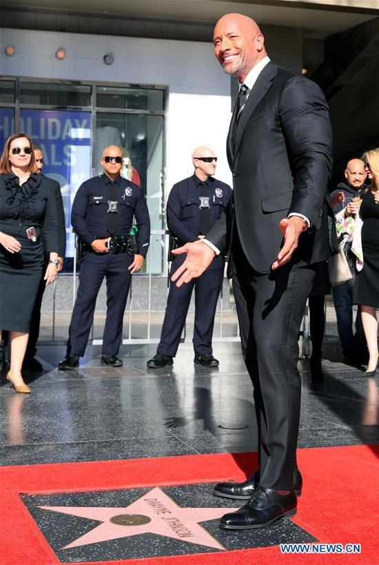 Dwayne Johnson poses for photos at his Hollywood Walk of Fame Star ceremony in Los Angeles, the United States, Dec. 13, 2017. Dwayne Johnson was honored with a star on the Hollywood Walk of Fame on Monday. (Xinhua/Li Ying)