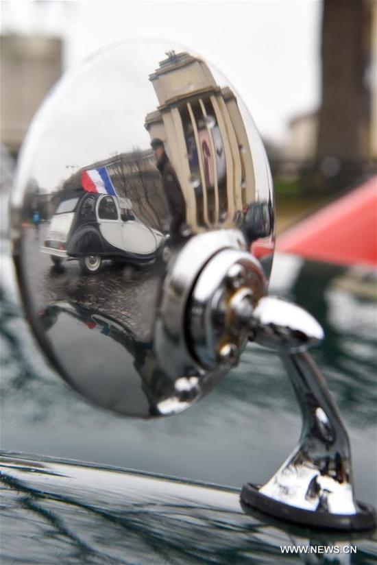 A vintage car with a flag of France is reflected on another car in Paris, France on Jan. 7, 2018. Hundreds of vintage cars, racing cars, jeeps, buses, motorcycles and bikes participated on Sunday in the 18th Paris Crossing of Classic Cars. (Xinhua/Chen Yichen)