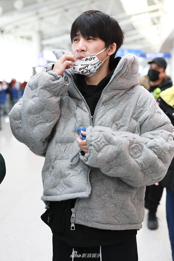 饮食属性曝光!张伟机场一路吃零食 白色印花口罩太私人了
