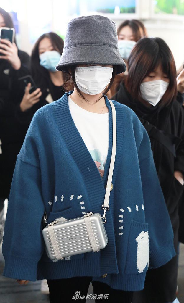 七头戴渔夫帽遮住精致的小脸 挎在精致的相机包上 针织开衫很老化