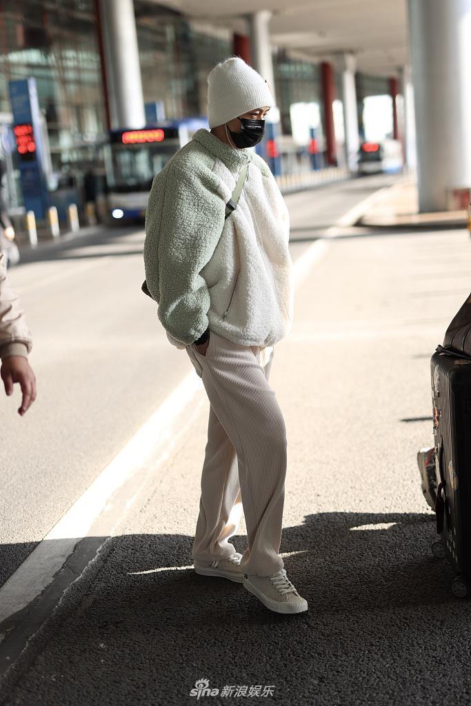 魏晨戴着笑脸帽 穿着毛绒衣服 他大步流星 他的手口袋