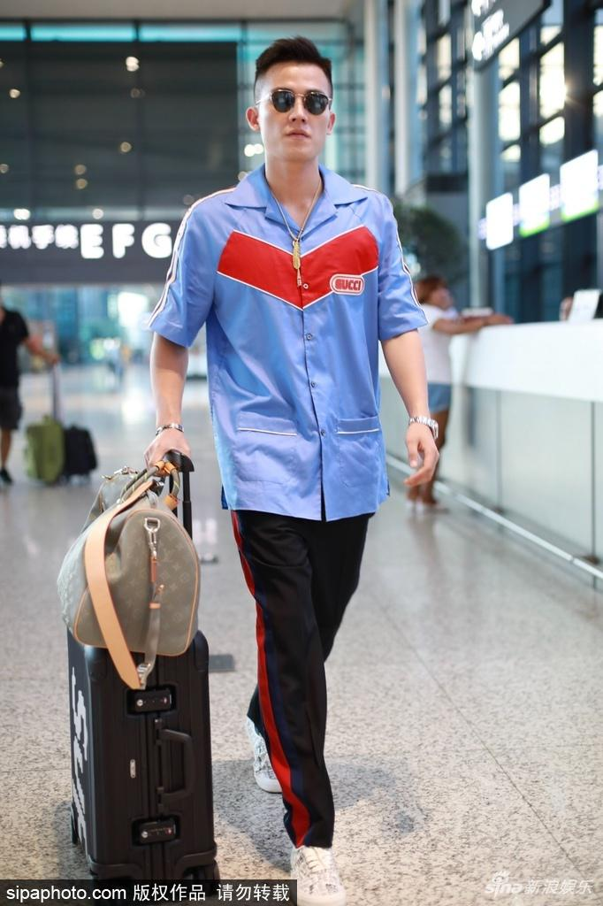 欧豪身着蓝色大号衬衫机场玩复古 看一张机票也超专注