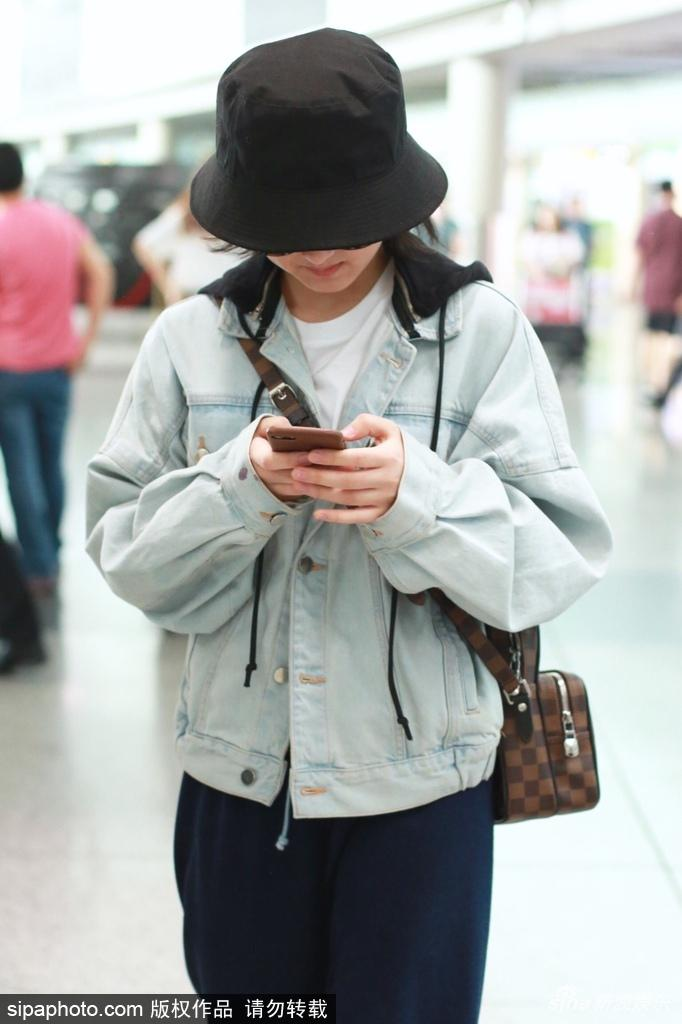 张子枫墨镜遮面休闲现身机场 一路低头专心玩手机