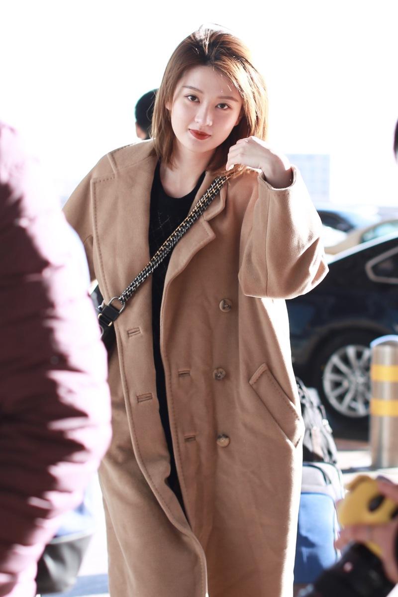 组图:乔欣穿卡其色大衣撩发魅力十足 蹲地系鞋带害羞捂脸超可爱